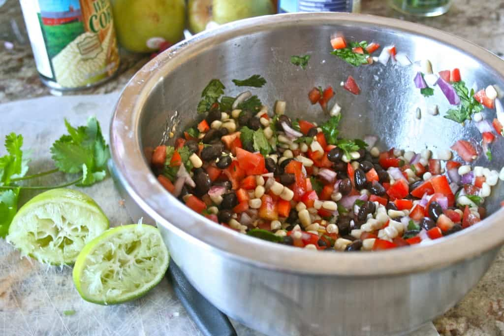 Side view of black bean salad in metal bowl, with juiced limes and fresh cilantro on the side.