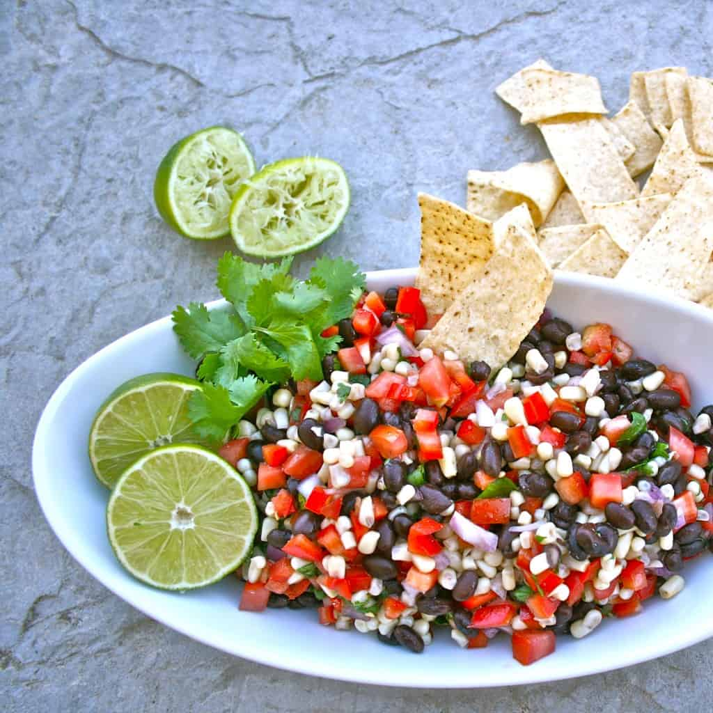 Overhead shot of southwest black bean salad in a white dish, garnished with limes, cilantro, and chips