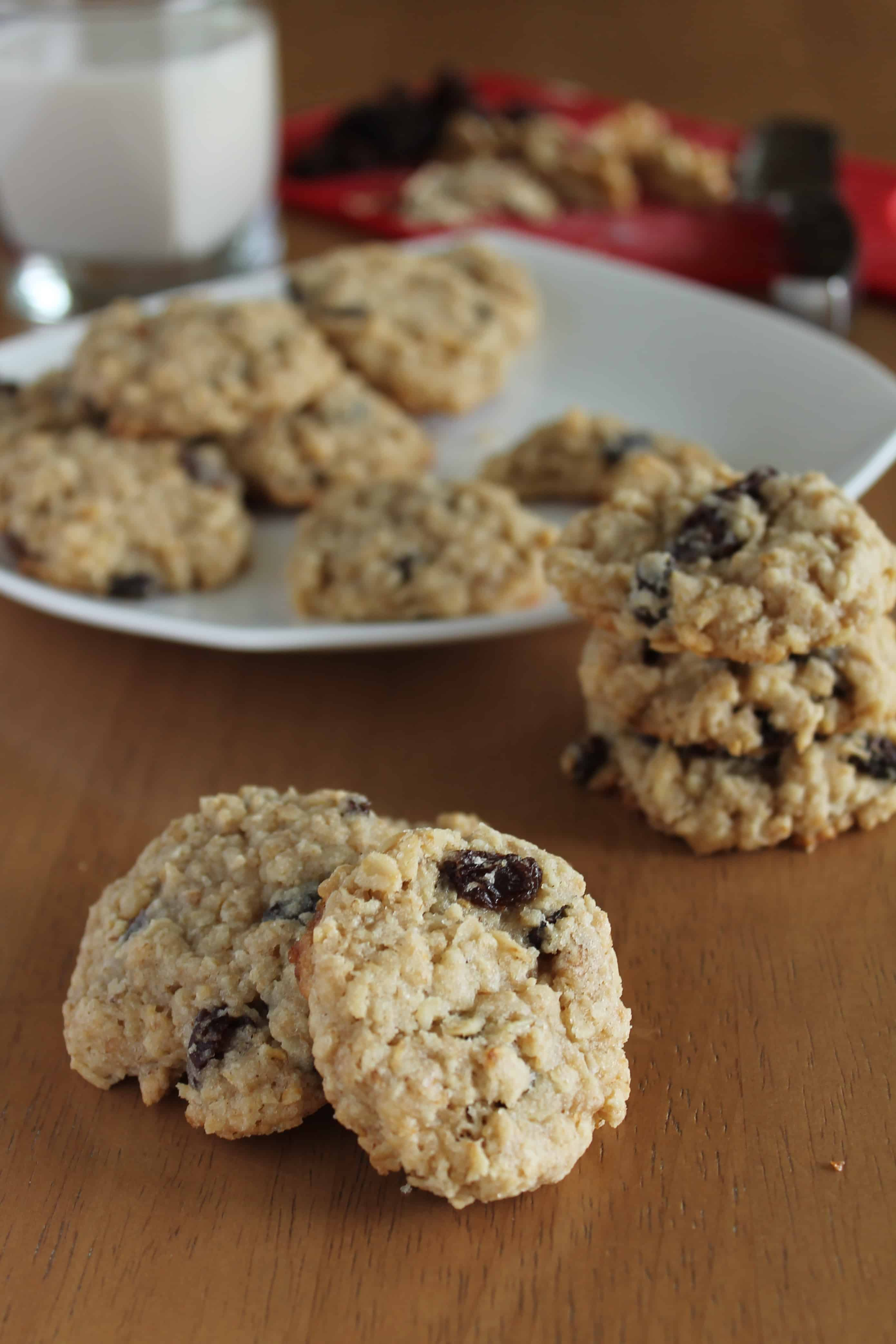 vegan oatmeal raisin cookies with wood backdrop and white plate in background