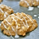 apple oatmeal cookies on cookie sheet pan drizzled with white icing