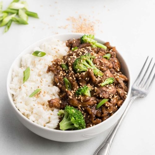 vegan beef and broccoli in white bowl with fork and white background
