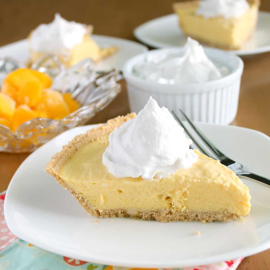 vegan mango cream pie on white plate with fork