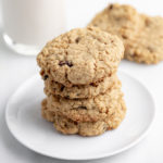 vegan oatmeal cookies stacked on white plate with nondairy milk and white marble background