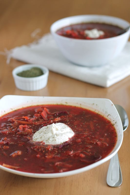 vegan borscht in white bowl topped with vegan sour cream