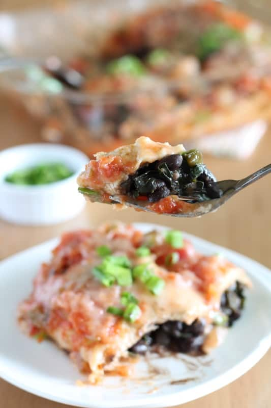 forkful of vegan black bean and kale enchiladas with white plate in the background