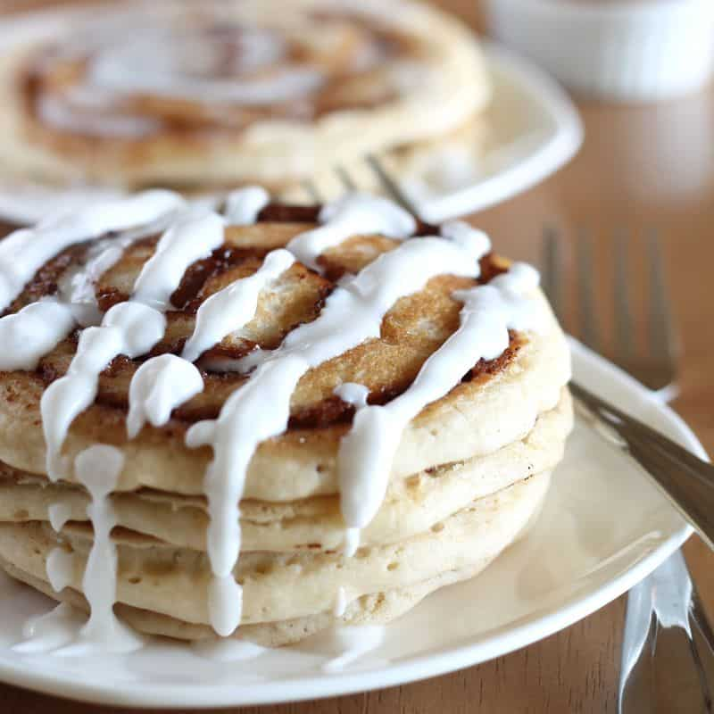 vegan cinnamon roll pancakes stacked on white plate with wood background