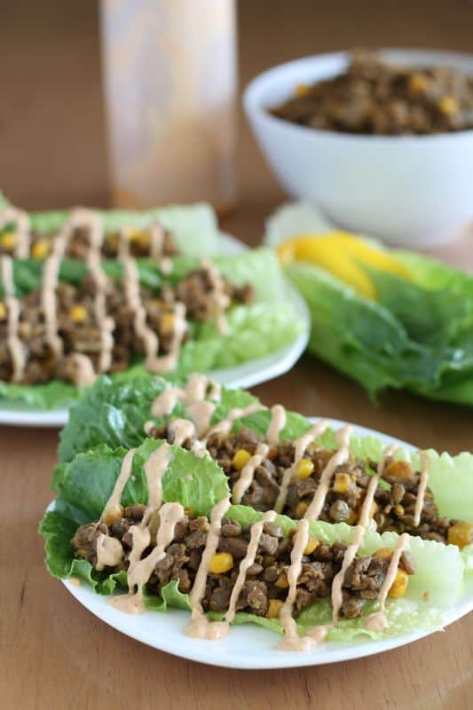 vegan lentil lettuce tacos on white plate with wooden background