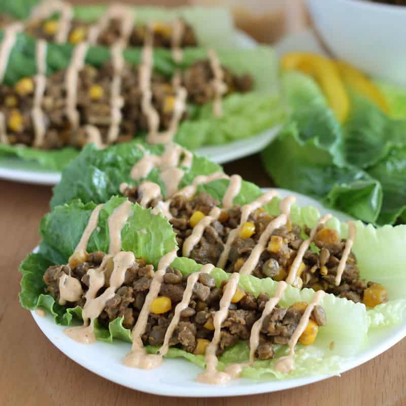 vegan lentil lettuce tacos on white plate with wood background