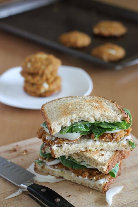 vegan tofu quinoa patties in sandwich with spinach and onion stacked on wood cutting board