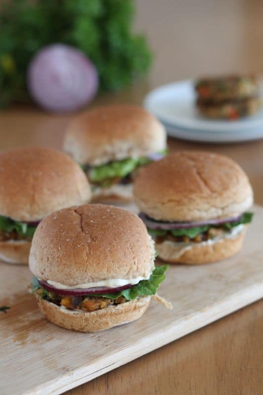 4 vegan veggie burger sliders on wood cutting board with lettuce and onion in background