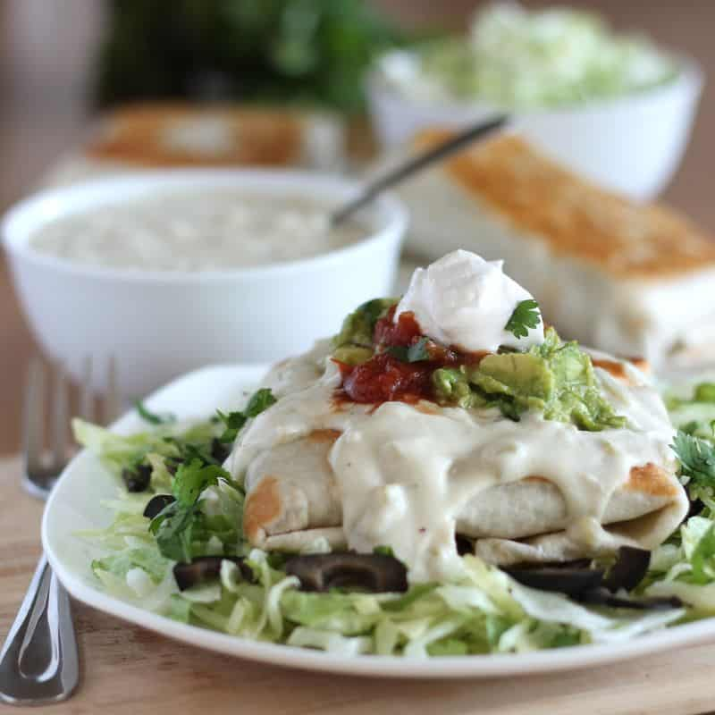 finished chimichanga on white plate with bed of lettuce, and cashew cream, guacamole, salsa, and sour cream toppings