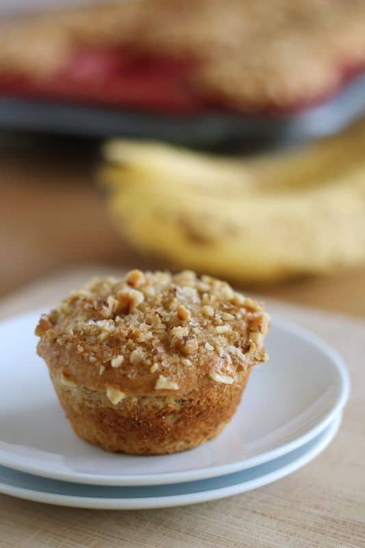 vegan banana muffin on white plate with speckled bananas in background