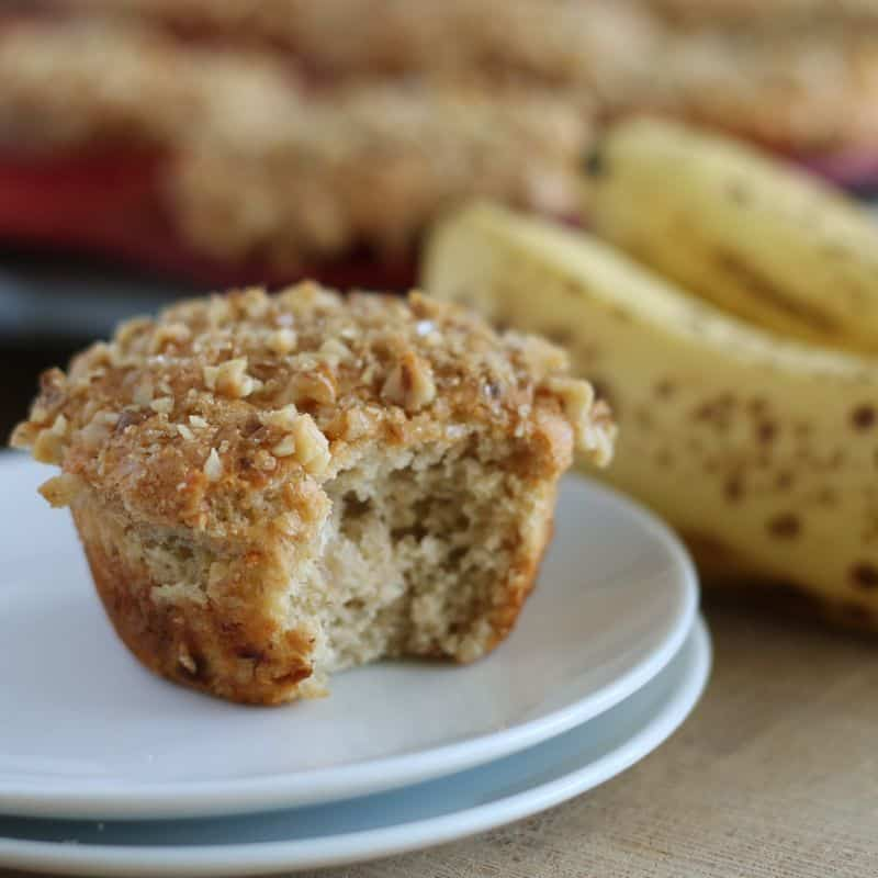 vegan banana muffin with bite taken out of it sitting on white plate with bananas in background