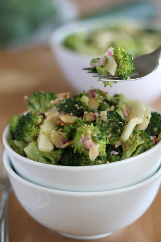 Forkful of broccoli cucumber salad coming from white bowl with wood background