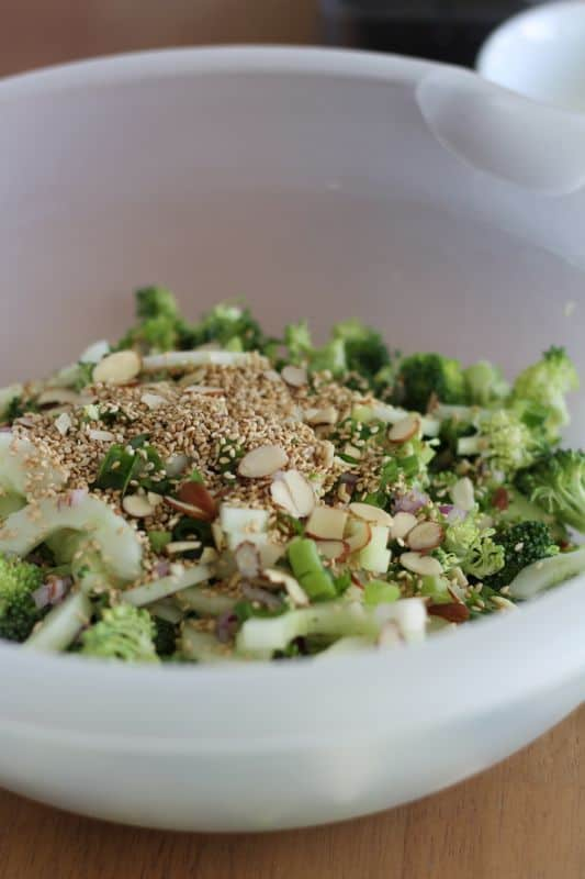 broccoli, cucumber, almonds, sesame seeds, and seasonings in mixing bowl with wood background