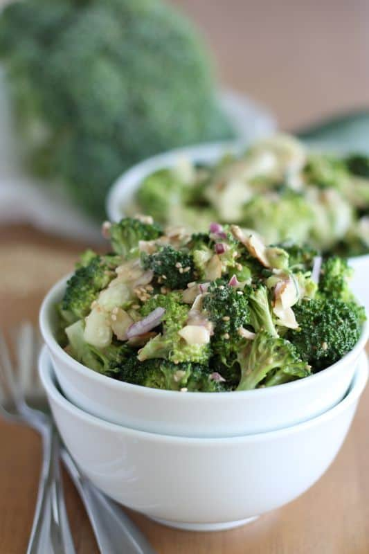 vegan asian style broccoli salad in white bowl with wood background