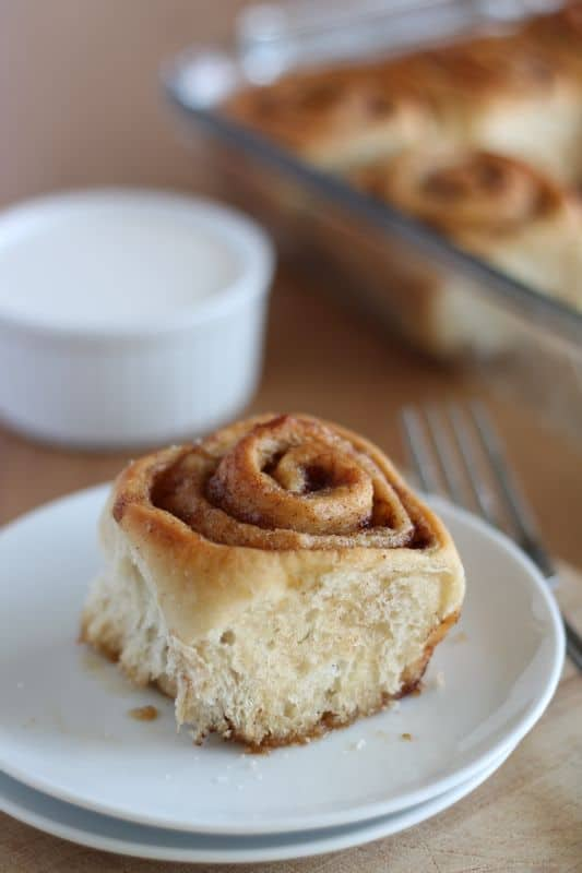 vegan cinnamon roll on white plate with wooden background