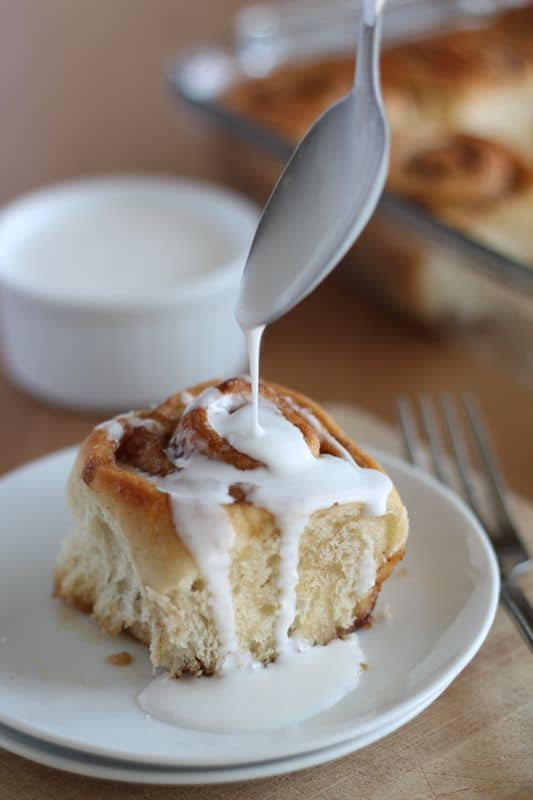 white coconut cream being spooned onto vegan cinnamon roll on white plate