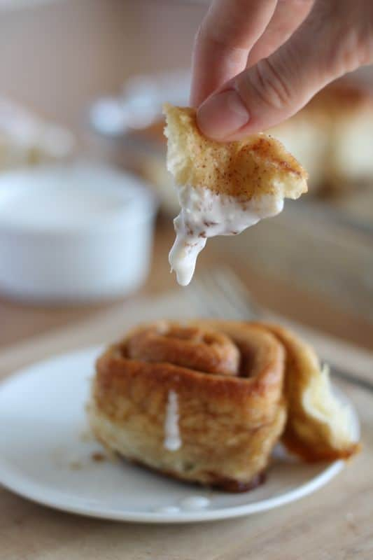 hand holding bite-sized piece of vegan cinnamon roll with white plate in background