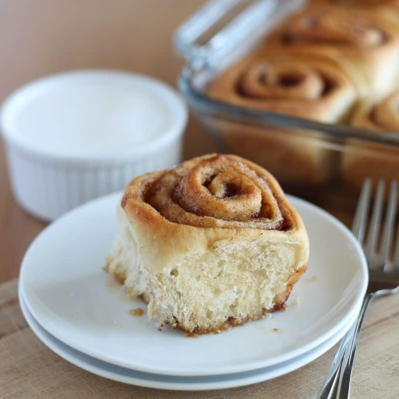vegan cinnamon roll on white plate with wood background
