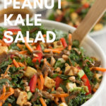 vegan peanut kale salad in white bowl with wooden utensil and text overlay