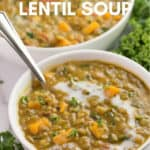 vegan curried lentil soup in a white bowl with marble background and kale on the side and white text overlay