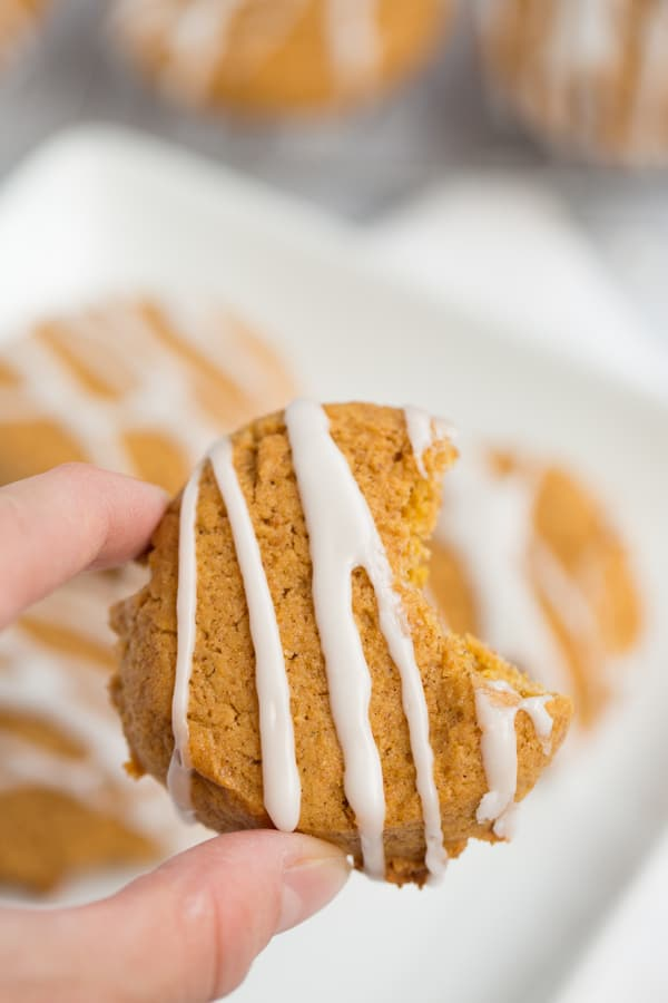 pumpkin cookie with white icing and bite taken out of the side, held by caucasian fingers