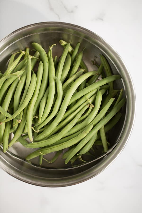 whole fresh green beans in steamer with white marble background