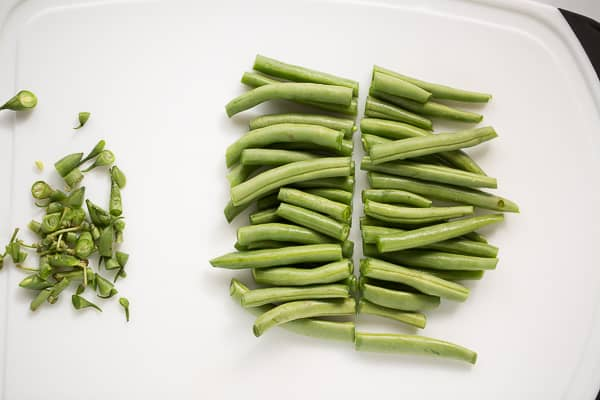 trimmed fresh green beans on white cutting board