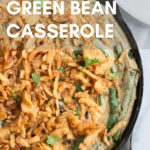 vegan green bean casserole in cast iron skillet with text overlay for Pinterest