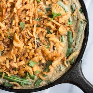 vegan green bean casserole topped with crispy fried onions in a cast iron skillet