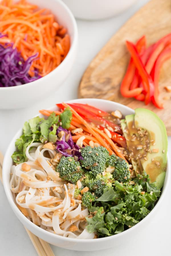 Vegan rainbow peanut noodle bowl -- arranged in white bowl with wood cutting board and second bowl in the background
