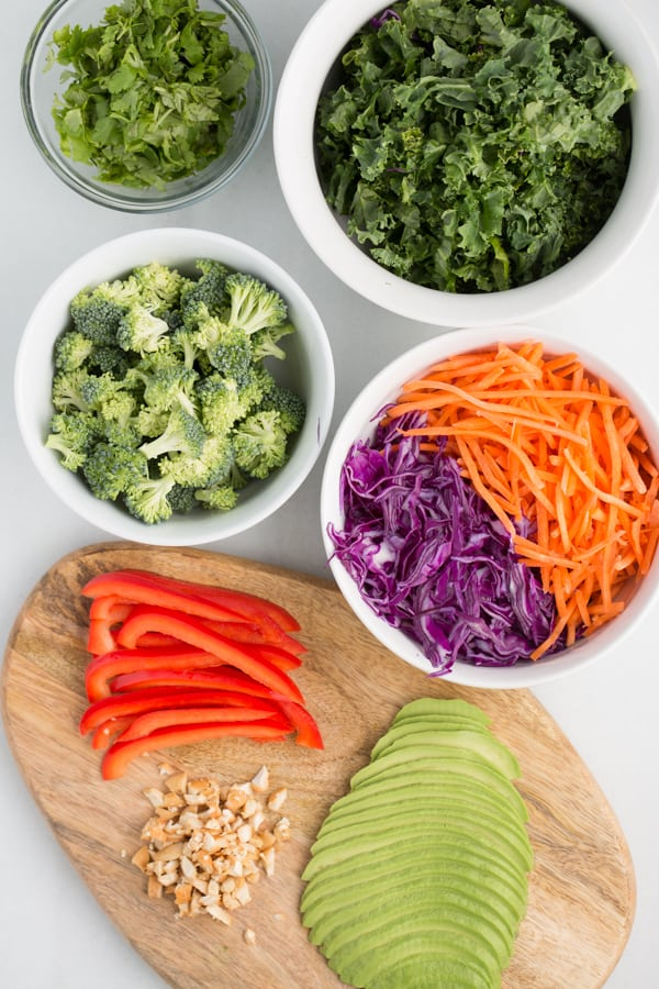 Kale, cilantro, broccoli, carrots, purple cabbage, peppers, crushed nuts, and avocado arranged in white bowls or on wood cutting board with white marble background