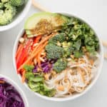 colorful vegetables with rice noodles and peanut sauce arranged in a white bowl with marble background
