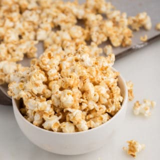 vegan caramel popcorn in white bowl with sheet pan in the background