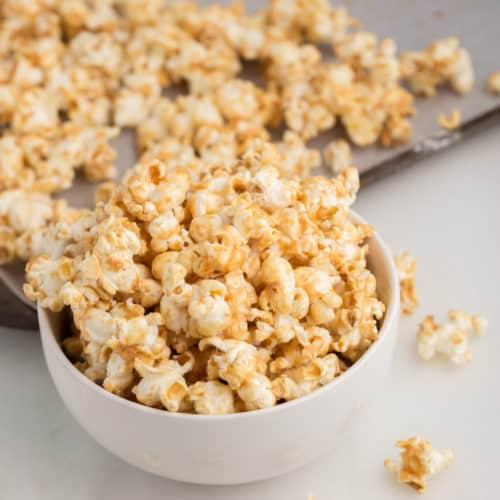 vegan caramel popcorn in white bowl with sheet pan in the background