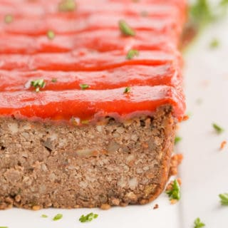 vegan meatloaf with maple tomato glaze and parsley on a white plate