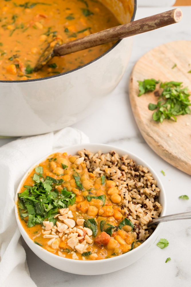 Vegan african peanut stew in white bowl with brown rice/quinoa and marble background