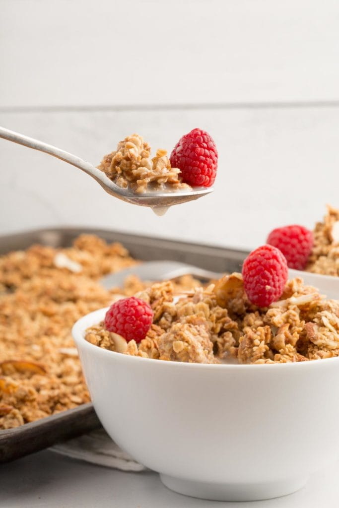 vegan almond granola in white bowl with spoon holding granola and red respberry above the bowl with white shiplap background