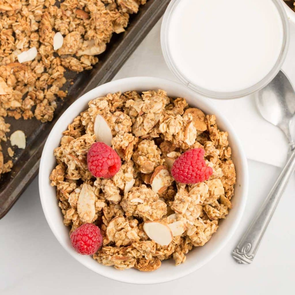 vegan almond butter granola garnished with raspberries in white bowl with white background