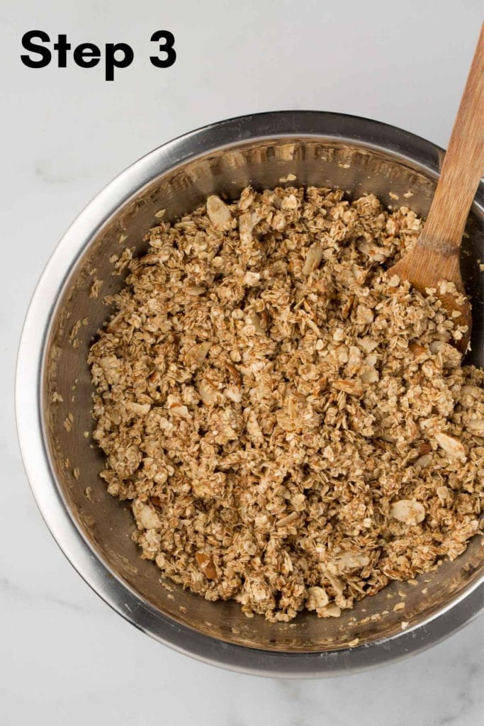 unbaked granola in a metal mixing bowl with wooden spoon and marble background