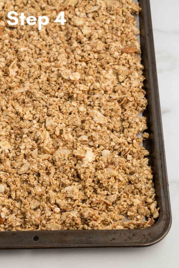 unbaked vegan granola in parchment lined baking sheet with marble background
