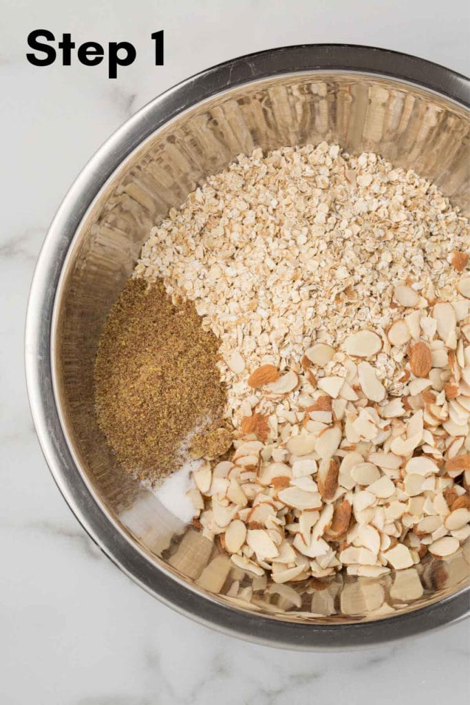 dry ingredients for granola in large metal bowl with marble background