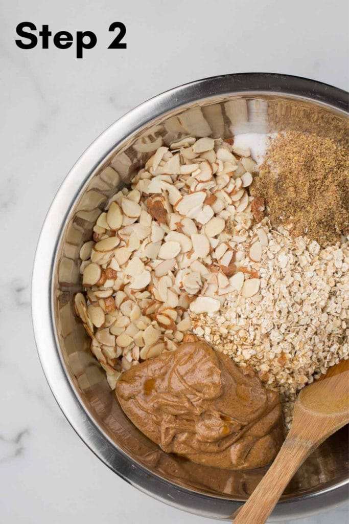 wet and dry ingredients, unmixed, in a metal bowl with a marble background and wooden spoon