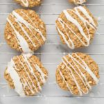 zig-zag iced vegan apple oatmeal cookies on wire rack with marble background