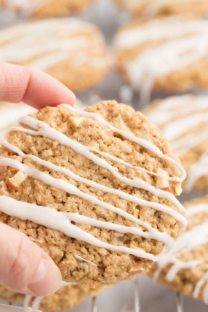 vegan apple oatmeal cookie being held between two fingers with blurry background of cookies