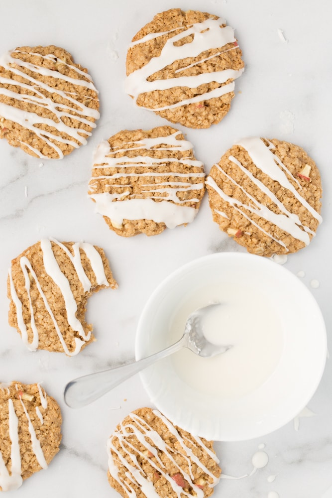 Vegan zig-zag iced apple oatmeal cookies with bowl of white icing to the side on marble background