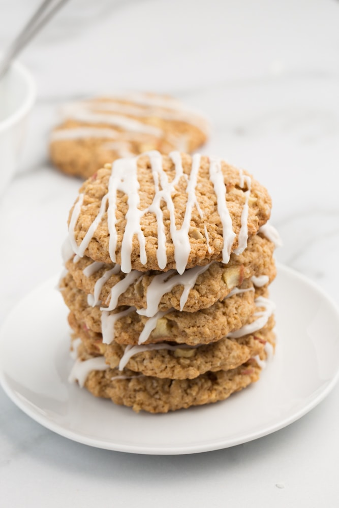 Vegan iced apple oatmeal cookies on white plate with marble background