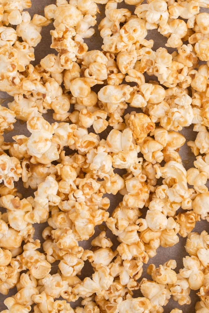 overhead view of vegan caramel popcorn in parchment lined cookie sheet