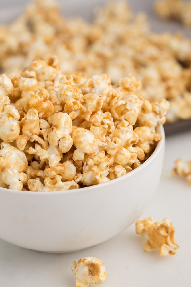 vegan caramel popcorn in white bowl with white marble background
